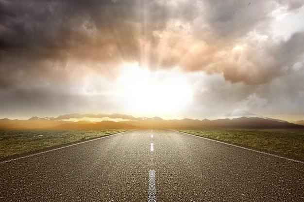 Асфальтовая дорога с зеленой травой и видом на горы
