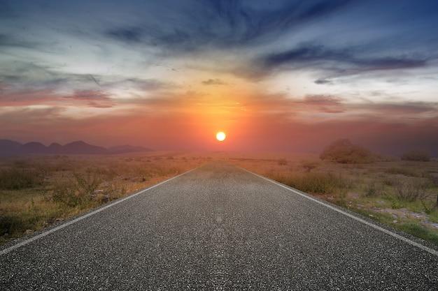 緑の草と日の出の空とアスファルト道路