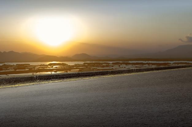 山の景色と夕焼け空のアスファルト道路