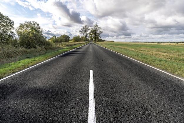 青い曇り空の下のフィールドに白い分割ストリップとアスファルト道路