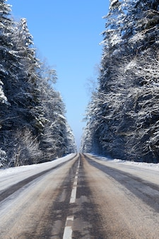 雪の下に白い道路標示のあるアスファルト道路、通過した車の雪の轍の一部が溶けた、冬の風景