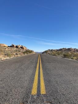 澄んだ青い空の下に黄色い線のあるアスファルト道路
