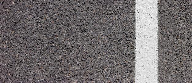오른쪽에 흰색 선이 있는 아스팔트 질감. 표시가 있는 도로 표면.