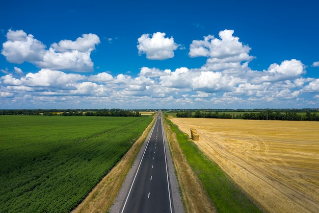 Asphalted narrow country road at the summer day aerial view.