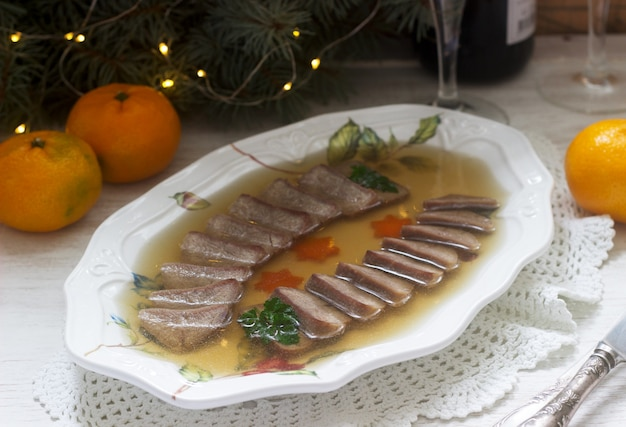Заливка языка, украшенная вареной морковью и петрушкой на праздничном столе