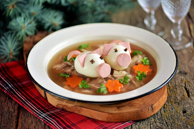 Aspic with meat, pork jelly is a festive traditional russian dish decorated with boiled eggs in the form of cute pigs.