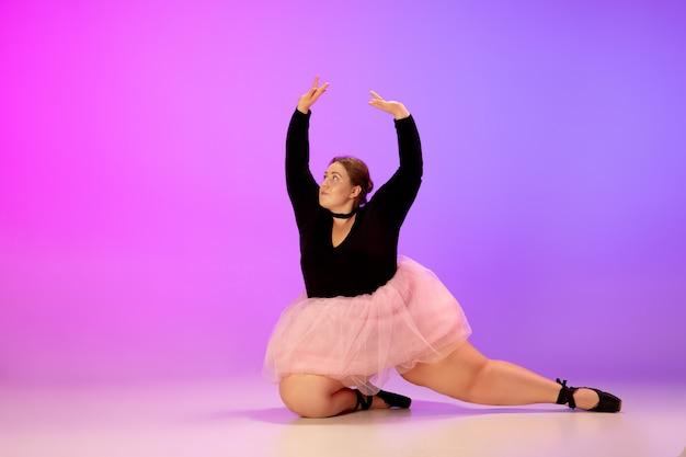 포부. 아름다운 백인 플러스 사이즈 모델은 네온 불빛 아래 그라데이션 보라색-분홍색 스튜디오 배경에서 발레 댄스를 연습합니다. 동기 부여, 포함, 꿈 및 성취의 개념.