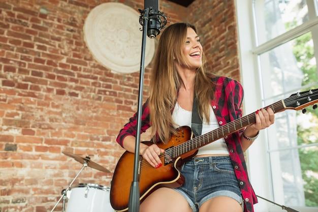 포부. 아름다운 여성은 로프트 직장이나 집에 앉아 음악을 녹음하고 노래하고 기타를 연주합니다.