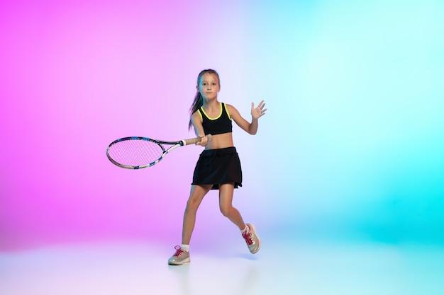 願望。ネオンの光のグラデーションの背景に分離された黒いスポーツウェアの小さなテニスの女の子。小さな白人モデル、運動と行動のスポーツキッズトレーニング。スポーツ、運動、子供の頃のコンセプト。