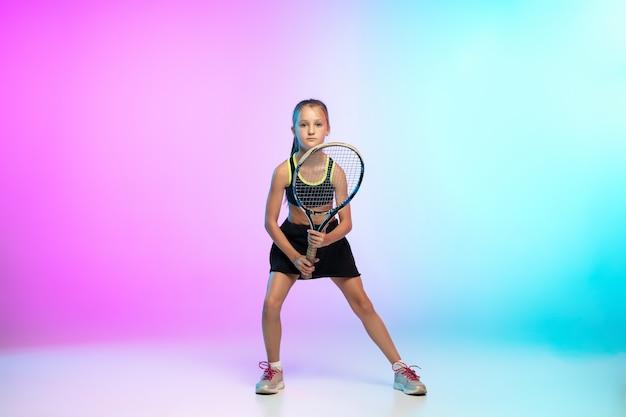포부. 그라데이션에 고립 된 검은 운동복에 작은 테니스 소녀