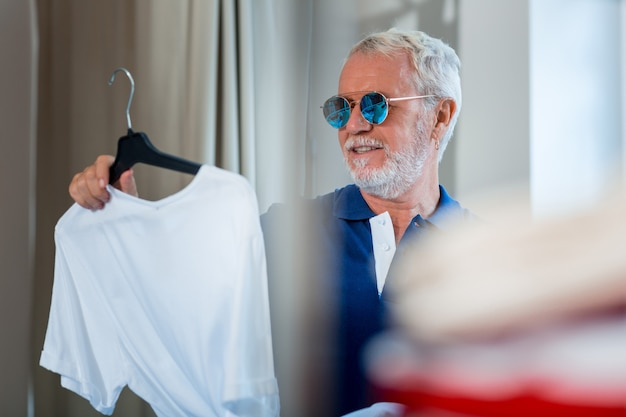 ファッションを志す。週末を過ごすのに最適な服装を考えながら白いtシャツを持っている陽気な老人のクローズアップ
