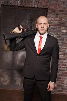 Убийца в костюме и красном галстуке держит пулемет