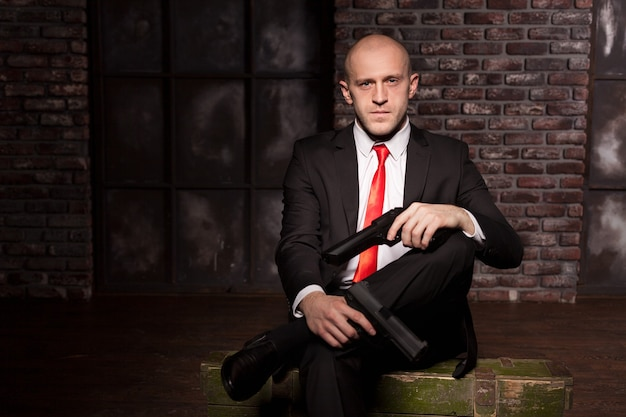 スーツを着た暗殺者とピストルを手に持った赤いネクタイ