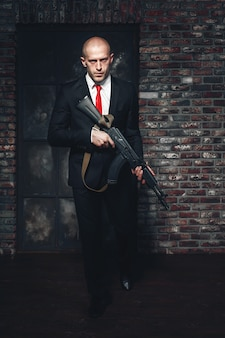 Assassin in suit and red tie holding machine gun in hands.