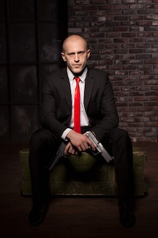 Assassin in suit and red tie holding pistol in hand