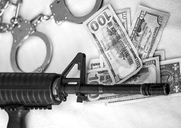 アサルトブラックライフル銃口。現代の自動ハイパワーライフルとドル通貨の警察の手錠の黒と白。スペースをコピーします。金融、犯罪、マフィア、テロバナー、武力紛争。米国
