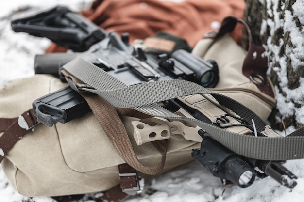 An assault rifle lies on a military briefcase in winter time.