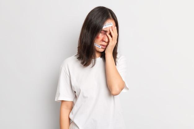 폭행당한 불쾌한 아시아 여성이 손으로 얼굴을 가리고 공포에 떨며 부상당한 압력 스탠드는 누군가가 위협하는 얼굴에 상처를 입혔습니다. 납치 및 학대 개념. 무방비 여성