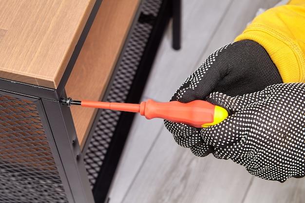 장갑 조립자는 집에서 플랫 팩 가구의 금속 프레임을 조립하면서 볼트를 조입니다.