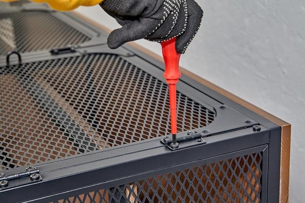 어셈블러는 플랫 팩 가구의 도어 힌지에있는 볼트를 드라이버로 조입니다.