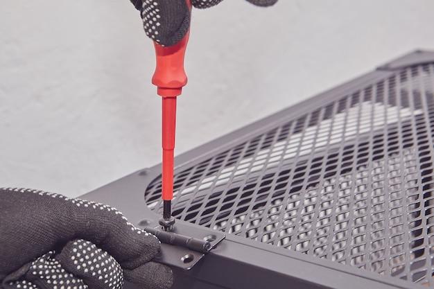 조립자는 플랫 팩 가구의 금속 프레임 도어에 나사를 조이고 있습니다.