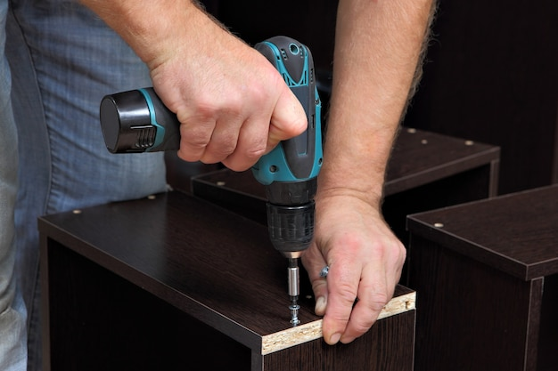 Assembling furniture, hands of carpenter with electric cordless screwdriver, tighten crew in drawers of chipboard.