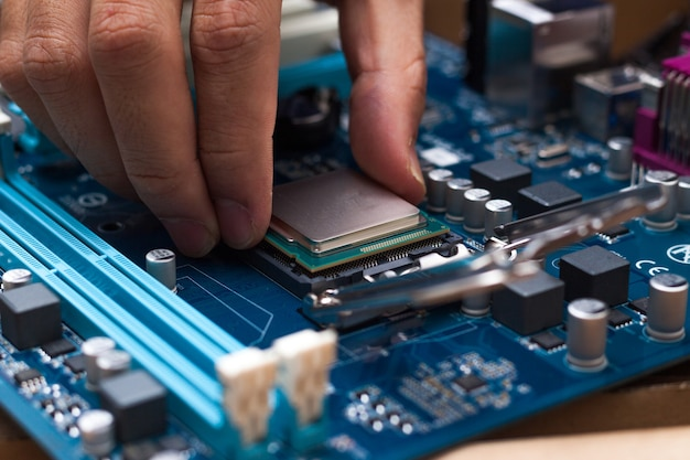 Assembling high performance personal computer, inserting cpu, processor into the motherboard socket, opened pc case in background, shallow depth of field, focus on hand