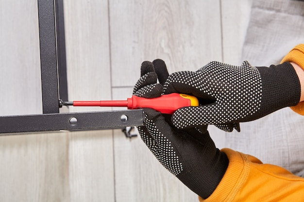 家具用の金属フレームを組み立て、手袋をはめた作業員がドライバーを使用してボルトを締めます。