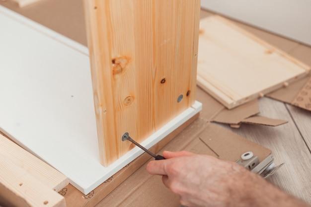 Сборка деревянной мебели вручную с помощью отвертки
