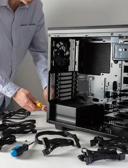 새 컴퓨터의 조립, 남성 마스터는 새 시스템 장치, 열린 케이스 및 케이블을 조립합니다.