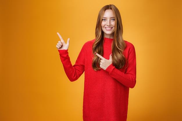 Напористая и услужливая очаровательная молодая ассистентка в красном вязаном платье с рыжими волосами дружелюбно и приятно улыбается, указывая в левый верхний угол, показывая интересную вещь над оранжевой стеной.