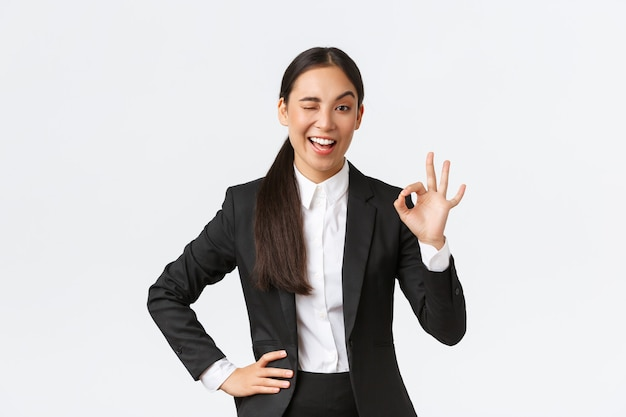 Assertive and confident young asian businesswoman got all under control, wink and show okay gesture to encourage deal is done, good job, nice work or approval gesture, standing pleased