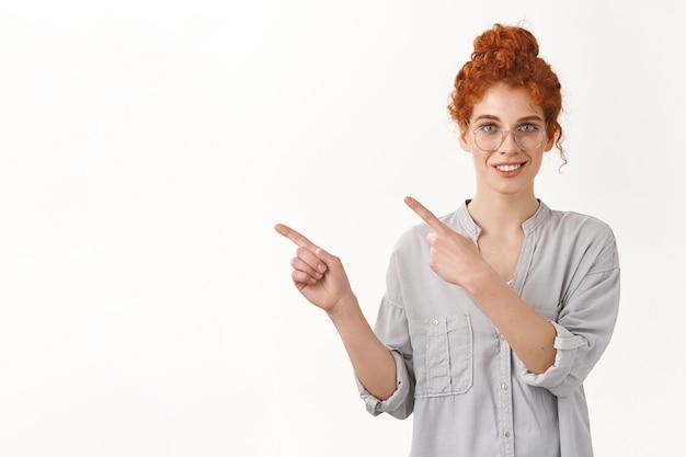 Assertivo bella donna europea dai capelli rossi tenera con i capelli ricci pettinati in una crocchia, introdurre profect sullo spazio bianco della copia in bianco, sorridente che punta a sinistra, promuovere il prodotto sul muro dello studio