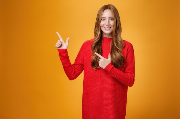 Assertivo e disponibile affascinante giovane assistente femminile in abito rosso lavorato a maglia con i capelli rossi sorridente amichevole e piacevole come indicando l'angolo in alto a sinistra, mostrando cosa interessante sul muro arancione