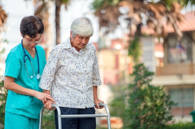 Помощь и уход со стороны врача пожилая женщина азиатского возраста или пожилая женщина-пациентка в отделении больницы, сидящая в инвалидном кресле: здоровая надежная медицинская идея