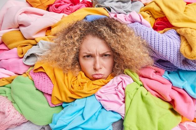 支援とボランティアのコンセプト。チャリティーや寄付のために集められた色とりどりの服に囲まれた落ち込んでいる疲れた女性。役に立たない古着の周りの不満な女性のポーズは何も着ていない
