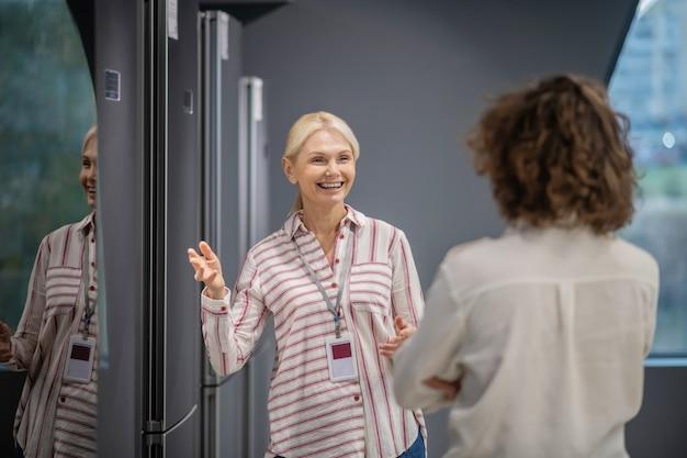 어시스턴트와 고객. 고객에게 새 냉장고를 보여주는 줄무늬 셔츠를 입은 점원