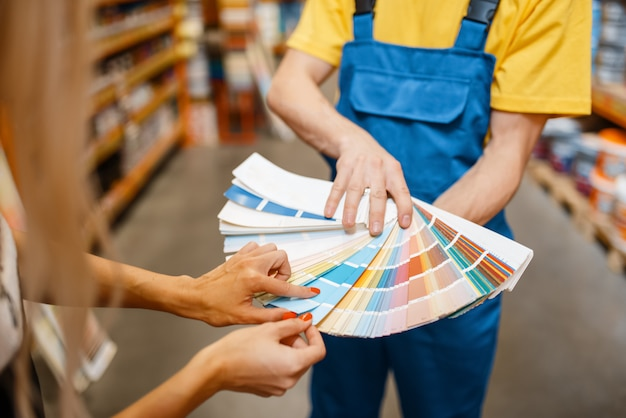 ハードウェアストアのカラーパレットを持つアシスタントと女性のお客様。スーパーマーケットの建物で買い物、制服を着た売り手とdiyショップの女性