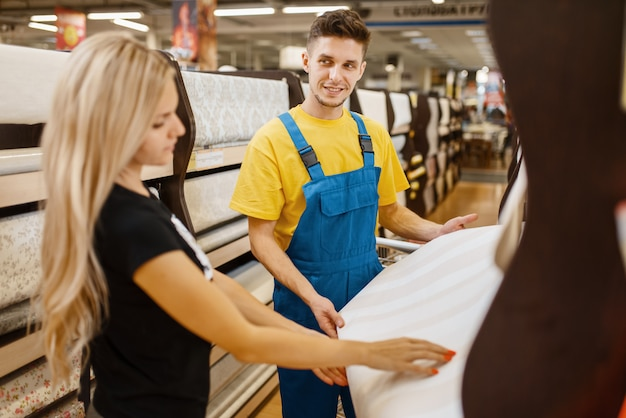 Assistant and female customer choosing wallpapers in hardware store. seller in uniform and woman in diy shop, shopping in building supermarket