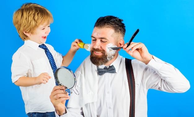 아빠의 어시스턴트. 아들과 아버지가 함께 수염을 면도하고 있습니다. 이발소. 수염 관리. 작은 이발사.