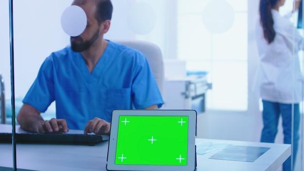 녹색 화면 디스플레이가 있는 의사 환자 엑스레이 및 태블릿 pc를 제공하는 도우미. 병원의 유리 벽을 통해 크로마 키가 있는 태블릿 컴퓨터의 전망.