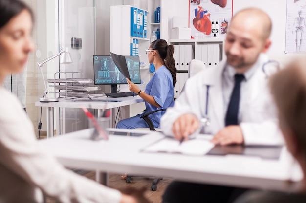 파란색 유니폼을 입은 조수는 병원 사무실에서 엑스레이 이미지를 보고 있습니다. 휠체어를 탄 장애인 노인 여성이 딸에게 진단을 설명하는 동안 흰색 코트를 입은 의사.