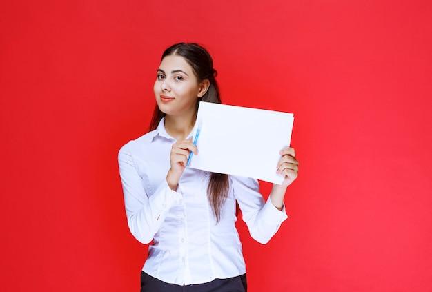 흰 셔츠를 입은 조수는 보고서와 수정 사항을 들고 시연합니다.