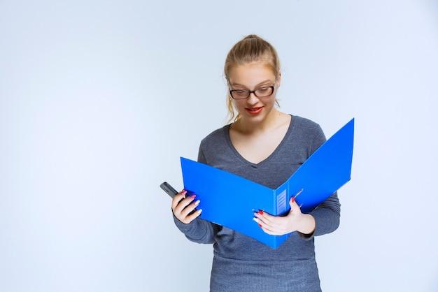 Помощник открывает синюю папку с отчетами и проверяет ее.