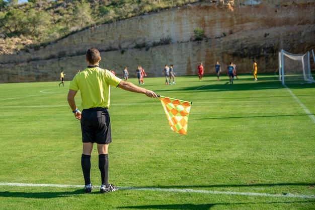 Помощник судьи в футбольном матче наблюдает за игрой