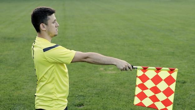 サッカーの試合中に副審がサイドラインに沿って移動する。サッカーの試合中に審判にオフサイドトラップの信号を送る副審の手。