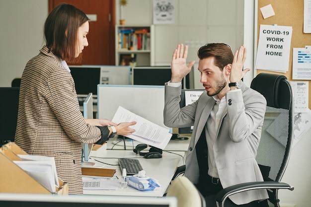 マネージャーに契約を示し、契約を説明するアシスタント