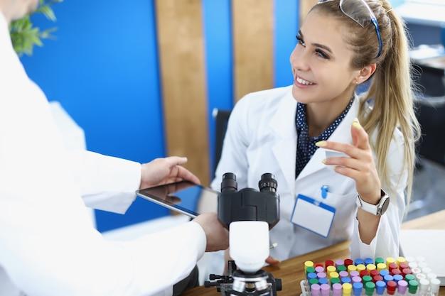 研究室のデジタルタブレット画面に女性化学者情報を表示するアシスタント