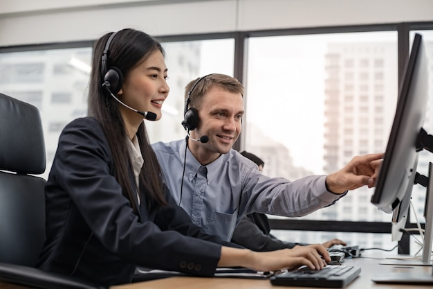 Assistant supervising the call center staff in the office. manager assistant staffs in a call center. customer service executive trainer assisting by team at office.