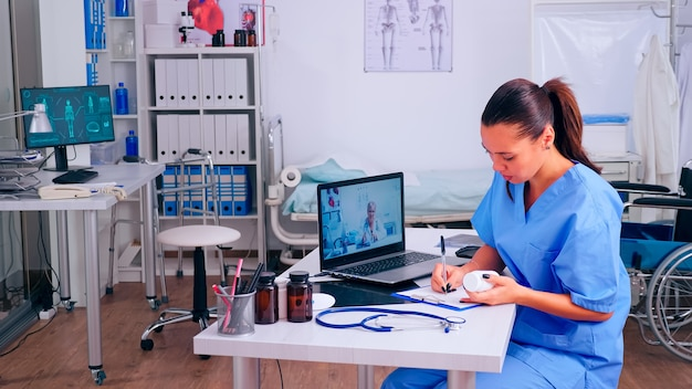 보조자는 화상 통화, 가상 건강 회의, 교육 웹 세미나 개념 중에 원격 의사의 조언을 듣고 메모합니다. 의사가 말하는 환자 진단, 온라인 회의